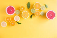 Creative Background Made Of Summer Tropical Fruits With Leaves, Grapefruit, Orange, Tangerine, Lemon, Lime On Pastel Yellow Background. Food Concept. Flat Lay, Top View, Copy Space
