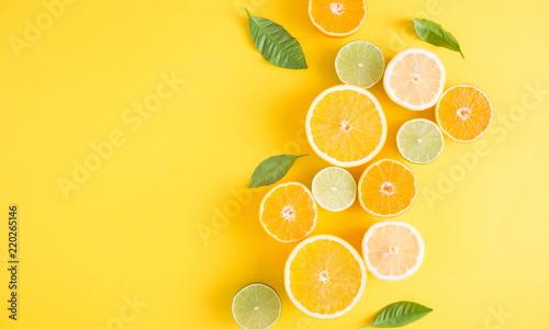 Twórczy tło wykonane z letnich owoców tropikalnych z liśćmi, grejpfruta, pomarańczy, mandarynki, cytryny, limonki na pastelowym żółtym tle. Koncepcja żywności. Leżał płasko, widok z góry, miejsce
