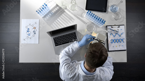 Fotografia  Scientist viewing samples under microscope, research for scientific article