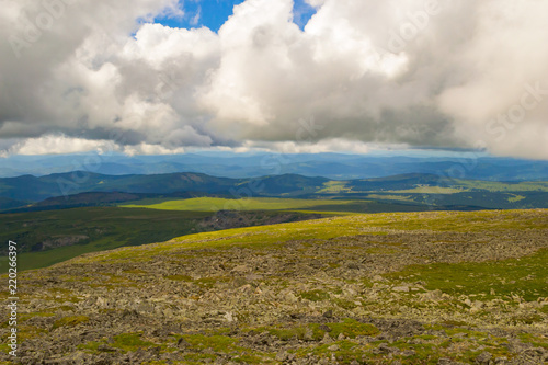 Fotobehang Landschap Landscape of green valley flooded with light with lush green grass, mountains, covered with stone and hills, a fresh summer day under a blue sky with white clouds and sun rays in Altai mountains