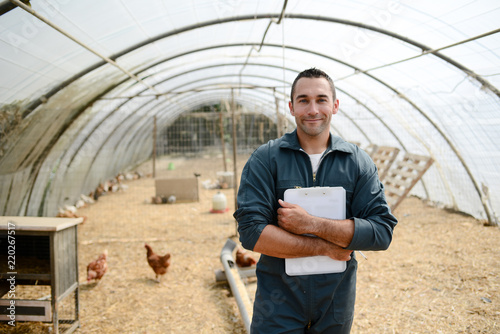 Fotografie, Obraz  portrait of handsome young farmer veterinarian taking care of poultry in a small