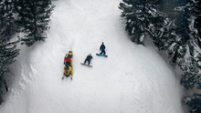Aerial View Of Injured Snowboarders And Snowmobile First Aid Motor Sledge Driving On Free Ride Mountain Slope Among Forest Pine Trees