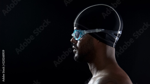 Male swimmer wearing goggles and preparing to jump into swimming pool, close-up