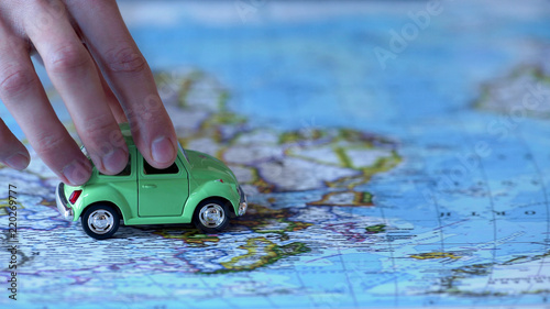 Fotografía  Human hand holding car model on world map, trip around Europe, vacation abroad