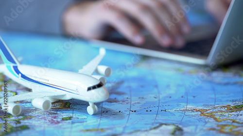 Obraz Airplane model closeup, defocused person booking flight tickets online on laptop - fototapety do salonu
