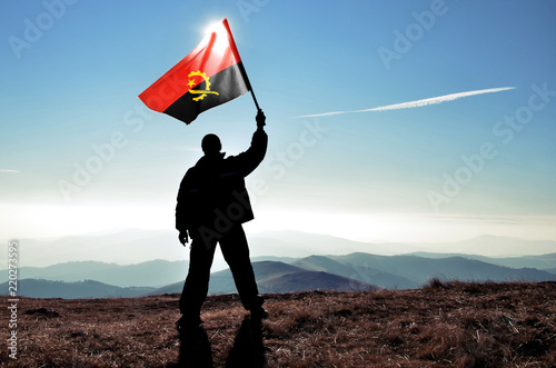 Photo Successful silhouette man winner waving Angola flag on top of the mountain peak