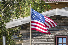The Flag Of USA Outside A Wooden Cabin