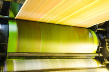 A Large Offset Printing Press Running A Long Roll Off Paper Over Its Rollers At High Speed.