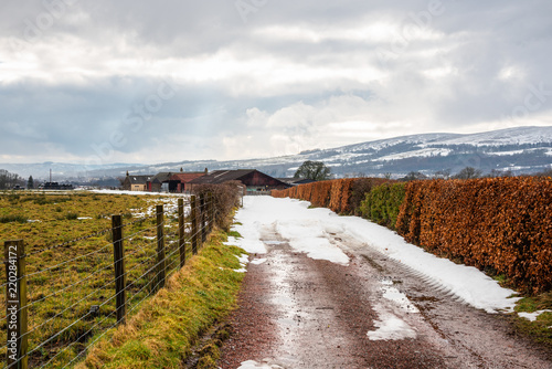 Foto op Aluminium Zalm Narrow Driveway to a Farm Partially Covered in Melting Snow in the Scottish Highlands on a Cloudy Winter Day