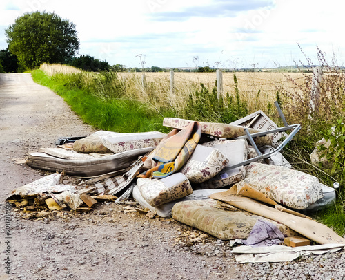 Heap of illegally dumped household rubbish left in a little used country lane Canvas Print