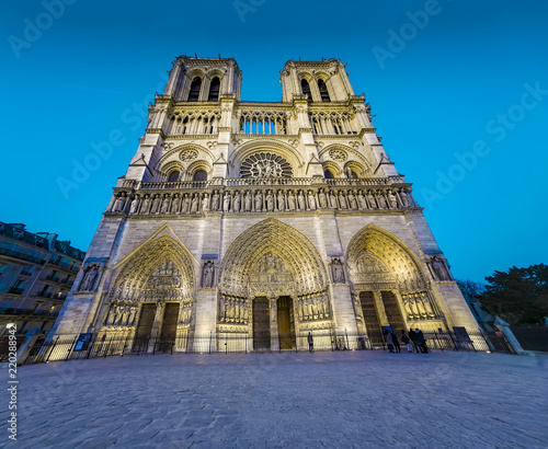 Photo View of Cathedral Notre Dame de Paris front entrance gate at night, twilight - a