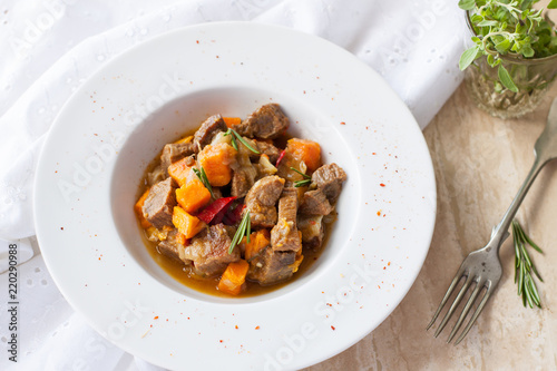Beef stew with butternut squash, pepper and onion decorated with fresh rosemary in white plate on marble table