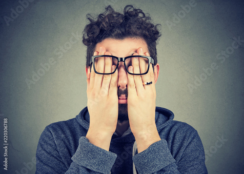 young man in glasses covering face eyes with both hands