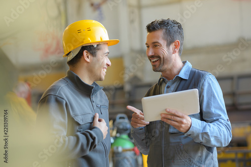 Valokuva workers talking and laughing at a factory