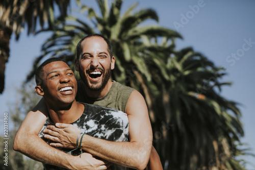 Gay couple hugging in the park Wallpaper Mural