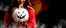 Happy Halloween. Beautiful Woman Costume And Holding Pumpkin. Copy Space On Dark Background.