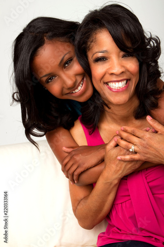 Fényképezés African American mother and daughter hugging and smiling.