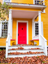 Porch Of Yellow New England House With Red Door And Fall Leaf Covered White Steps