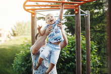 Young Father And A Blond Boy In Blue T-shirts Climb The Stairs At The Children's Playground In The Summer.