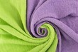canvas print picture - Twisted textiles. Background with a wave of light green and purple towels. Background for design.
