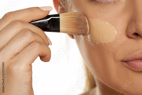 Fotografiet Young woman applying liquid foundation with brush on white background