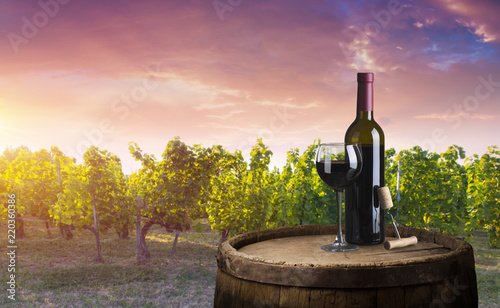 Deurstickers Toscane Red wine bottle and wine glass on wodden barrel. Beautiful Tuscany background