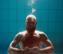 Portrait Of Muscles Beard Yoga Man Underwater In The Swimming Pool