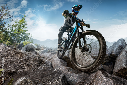 Stampa su Tela Mountain biker on stone trail. Male cyclist rides the rock
