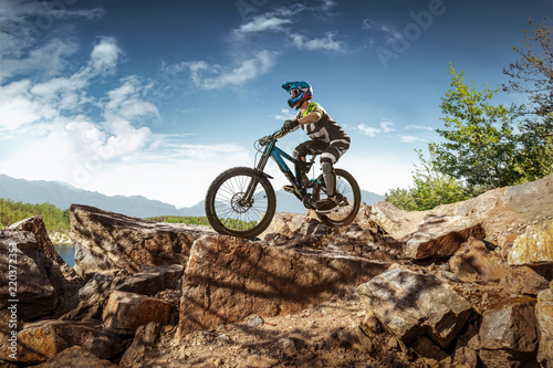 Foto auf Gartenposter Blau Jeans Mountain biker on stone trail. Male cyclist rides the rock