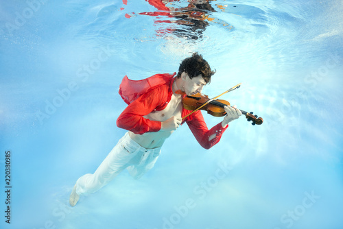 Photo Teenager plays the violin underwater