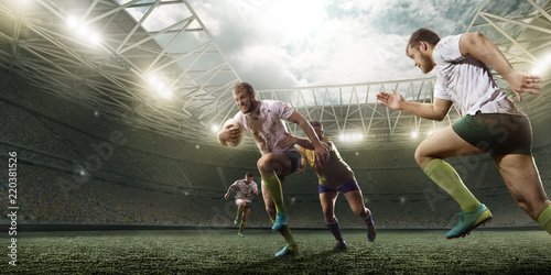 Fototapeta Rugby players fight for the ball on professional rugby stadium