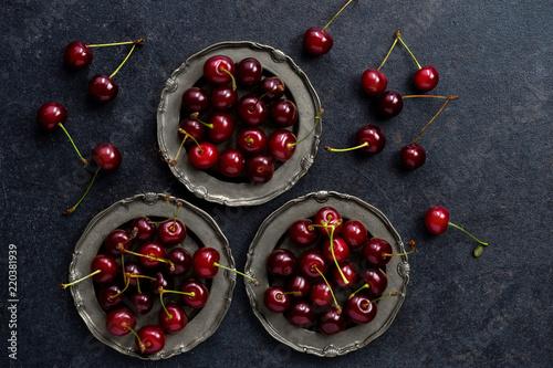 red cherry in vintage silver plate over dark grunge background.
