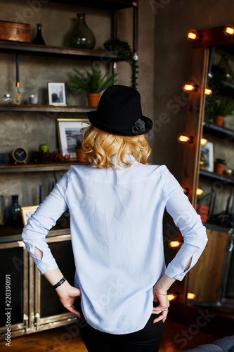 Photo sur Toile Hong-Kong Blonde in a black hat and a blue blouse stands with his back to the camera, hands in trouser pockets