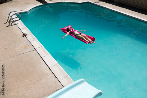 Cute young woman in a bikini on a raft in a swimming pool, slide in the