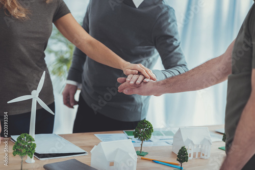 Obraz Great work. Close up of attractive male and female hands putting together and holding above models - fototapety do salonu