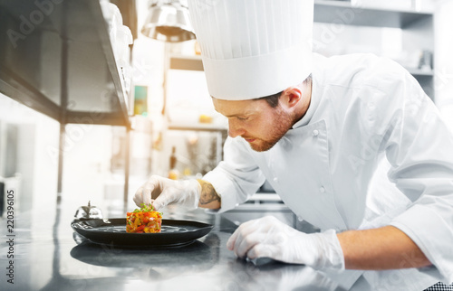 Fototapeta food cooking, profession and people concept - happy male chef cook serving and garnishing stewed vegetables on plate at restaurant kitchen obraz
