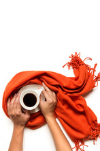 Cup Of Coffee Wrapped In A Gray Scarf And Female Hands On A White Background Is Isolated. Autumn Or Winter Concept. Flat Lay, Top View