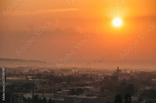 Golden sunrise above the city in the mist