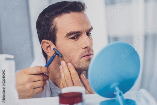 Man with razor. Dark-haired good-looking man holding razor in his hand whie shaving his face in the bathroom