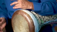 Closeup Of Hands Playing Slow Rhythm On Clay Doumbek With Fish Skin Head.