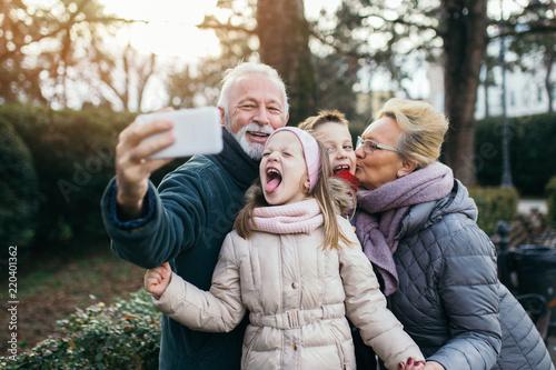 Obraz Grandparents taking selfie photo with their grandchildren in city park. - fototapety do salonu