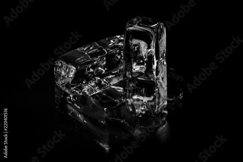 Photo  Four melting ice blocks isolated on the black background