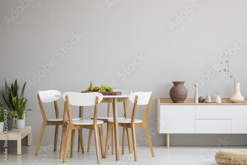 Fotomural  Wooden chairs at table in grey dining room interior with plants and white cupboard
