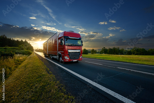 Vászonkép Red truck arriving on the asphalt road in rural landscape in the rays of the sun