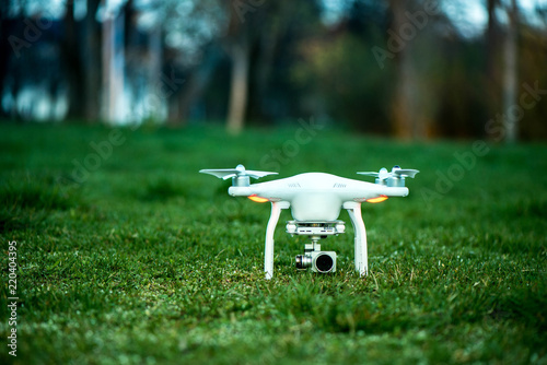 Photo White quadrocopter, is ready for take off to fly high in the air, to take photos and record footage from above
