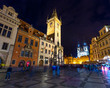Thousands of tourists walking in spring night on the Old Town square with Tyn Church.