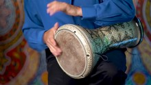 Closeup Of Hands Playing Fast Rhythm On Doumbek Drumming Slow Rhythm With Arabic Background.