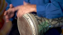 Closeup Of Hands Playing Roll On Doumbek Drumming Slow Rhythm With Arabic Background.