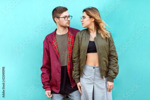 Fotografia fashion couple standing posing near blue wall