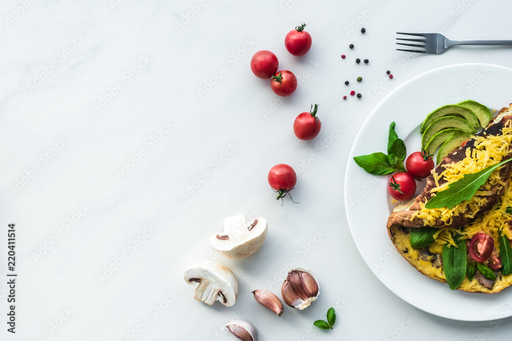 Fototapety, obrazy: top view of homemade omelette with cherry tomatoes, avocado pieces and cutlery on white marble surface